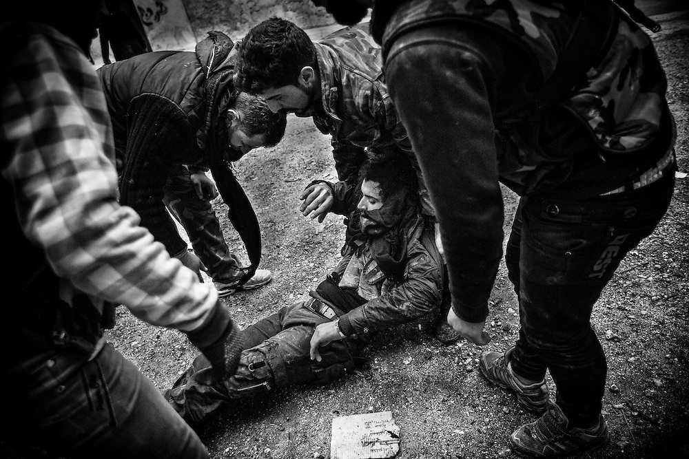 A wounded soldier of the Free Syrian Army is being carried by his comrades as he was hit during gun battle in Aleppo, Syria.
