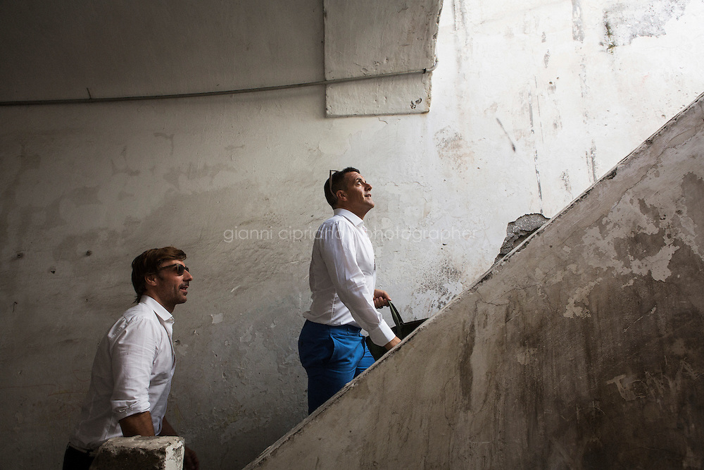 TORRE DEL GRECO, ITALY - 13 JULY 2016: (R-L) Amedeo Scognamiglio, master-carver and founder of Amedeo, a collection of modern-day Cameos and avant-garde artisan jewels, and his business partner and long-time childhood friend Roberto Faraone Mennella, walk up the stairs leading to the workshops of Francesco Scognamiglio, a cameo carver that works with Amedeo, in Torre del Greco, Italy, on July 13th 2016.<br /> <br /> Amedeo Scognamiglio learned the art of carving of cameos at the age of 16 years old in his father's company (M+M Scognamiglio), continuing an artistic manufacturing tradition of a six generations family of coral and cameo manufacturers dating back to the early 1800s in Torre del Greco, a town at the foot of Mount Vesuvius, Italy. Amedeo's design philosophy aims at a contemporary approach to the ancient art of cameo making, through alternative materials, unexpected ideas and smile-triggering designs. In 2001, Amedeo Scognamiglio partnered with his long-time childhood friend Roberto Faraone Mennella to create a fine jewelry line called Faraone Mennella by R.F.M.A.S. Group.The designer duo created a line that brings together the quality and craftsmanship of fine Italian jewelry to the world of fashion accessories. In 2006, the opening of AMEDEO, a Boutique on the chic Upper East Side in NYC, dedicated to the Designer's vision of Cameos, and followed shortly after by another opening in Capri, Italy.