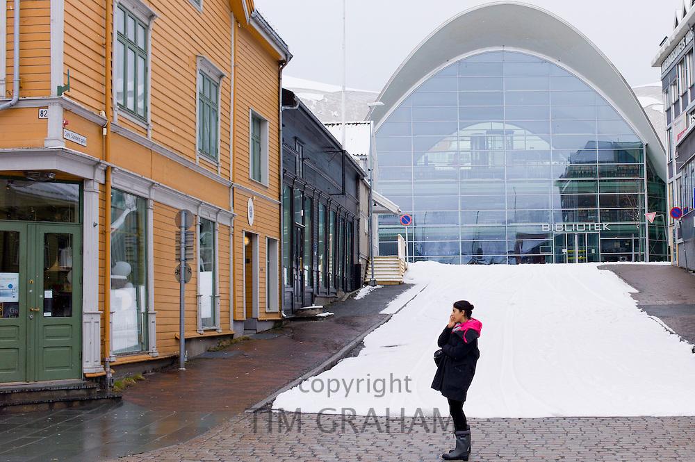 Local woman using mobile phone in street scene in Tromsoya, Tromso,  Arctic Circle in Northern Norway