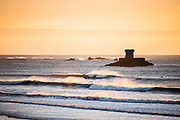 Golden sunlight bouncing off the waves as people surf in front of La Rocco Tower at St Ouen's Bay, Jersey, CI at sunset