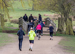 """© Licensed to London News Pictures. 26/03/2021. London, UK. Members of the public enjoy a walk in Richmond Park, South West London ahead of the end of the """"Stay at Home"""" advice from Monday. On Monday 29 March, the """"Stay at Home"""" advice will end with people being allowed to meet up within the """"rule of six"""". Playing golf, tennis and organised outdoor sports will also be allowed as England starts to unlock after a year of Covid-19 restrictions. Photo credit: Alex Lentati/LNP"""