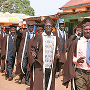 CAPTION: Bespectacled Edward Okiror of World Renew Uganda marches through the town of Kaberamaido, shoulder to shoulder with other graduands trained by Timothy Leadership Training (TLT). LOCATION: Kaberamaido, Kaberamaido District, Uganda. INDIVIDUAL(S) PHOTOGRAPHED: Edward Okiror (in glasses) and TLT graduands.