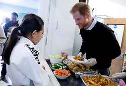 The Duke of Sussex serves a hot healthy lunch to children during a visit to Streatham Youth and Community Trust's John Corfield Centre to see a 'Fit and Fed' February half-term holiday activity programme.