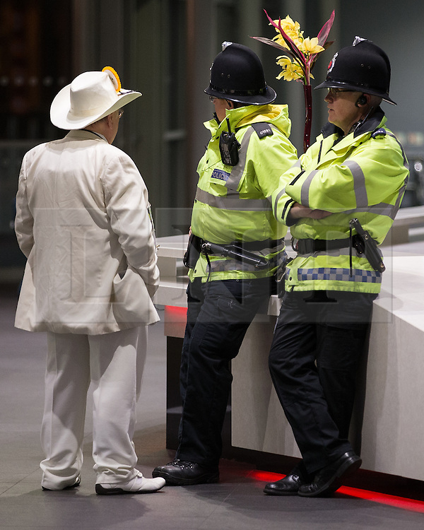 """© Licensed to London News Pictures . 14/02/2014 . Manchester , UK . The Monster Raving Loony Party 's Alan """" Howling Laud """" Hope talking with two policemen . The count for the Wythenshawe and Sale East by-election , at Manchester Central this evening . Photo credit : Joel Goodman/LNP"""