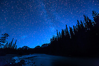 A long exposure image of the night sky over Waterfowl Lakes on the Icefields Parkway in Banff National Park. It was extremely dark and many more stars than we can normally see were visible in the sky. The trees and mountains reflecting in the water were an added bonus.<br /> <br /> ©2015, Sean Phillips<br /> http://www.RiverwoodPhotography.com