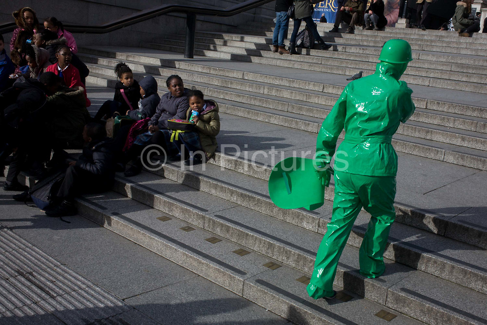 Green busker person walks past schoolchildren with pigeon seemingly perched on shoulder. The person whose face is unseen, walks up the steps in London's Trafalgar Square, about to take up position and entertain the crowds of tourists and kids in winter sunshine. The kids look on with interest as they eat lunch, crouched on the steps at this famous landmark. The costume appears to be shiny plastic and the false perspective confuses us with the bird on the shoulder.
