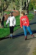 Friends age 21 rollerblading around Lake Calhoun.  Minneapolis  Minnesota USA