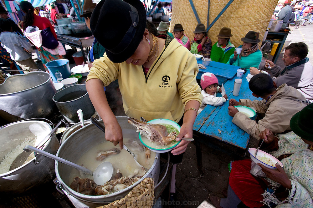 A woman prepares sheep's head soup for sale in the colorful weekly market at Zumbagua in Ecuador.