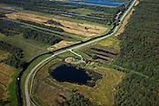Nederland, Overijssel, Gemeente Steenwijkerland, 08-09-2009. Nationaal Park De Weerribben, de enige doorgaande weg door het gebied, de Hoogeweg met watermolen (gebruikt voor het bemalen van een inmiddels verdwenen polder). Het landschap is het resultaat van het winnen van turf, na het steken van de turf (waardoor de 'trekgaten' ontstonden) werd dit te drogen gelegd op legakkers (de 'ribben'). Tegenwoordig vindt er rietteelt plaats (dekriet). Het laagveen gebied verdroogd en verruigt waardoor veenheiden of moerasbossen ontstaan. .The National Park Weerribben. The landscape is the result of the extraction of peat, after digging the peat (creating  the 'pull holes'), it was to layed to dry on fields (the 'ribs'). As the paet bog fields become more dry, peat swamp forests occur..toeslag); aerial photo (additional fee required); .foto Siebe Swart / photo Siebe Swart