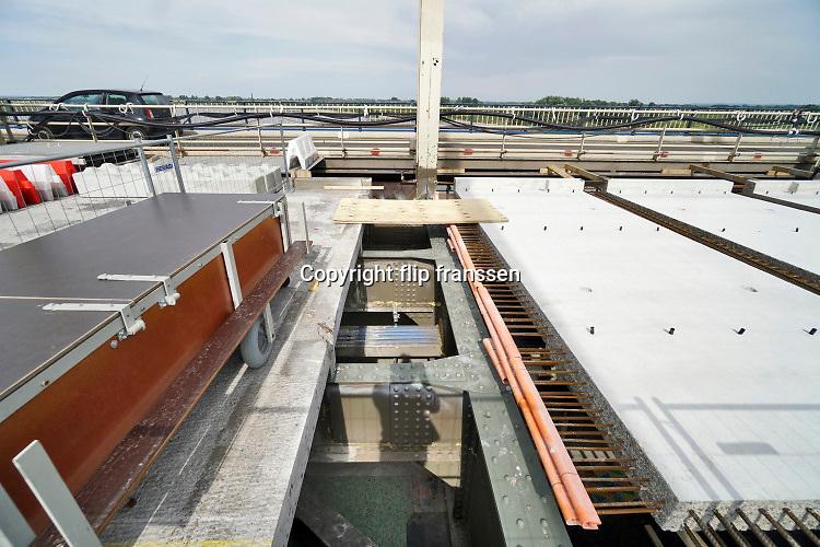 Nederland, Nijmegen, 30-6-2019 Aannemer KWS doet groot onderhoud aan de oude, iconische Waalbrug . De brug wordt de komene maanden grondig gerenoveerd en opgeknapt. Het bleek dat de oude verf chroom6 bevat waardoor de renovatie is uitgesteld vanwege extra veiligheidsmaatregelen. De brug is gebouwd in 1936 en was toen de langste boogbrug van Europa . Eerst wordt de onderkant onder handen genomen, en later wordt de brug opnieuw geschilderd als ook duidelijk is hoe de oude verf het beste verwijdert kan worden . Het verkeer kan mondjesmaat over de brug en dat veroorzaakt veel file en oponthoud op de A325 en N325 Foto: Flip Franssen