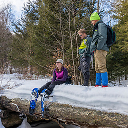Hikers take a break from snowshoeing up Huckleberry Mountain in South Johnsburg, New York. Adirondack Mountains.