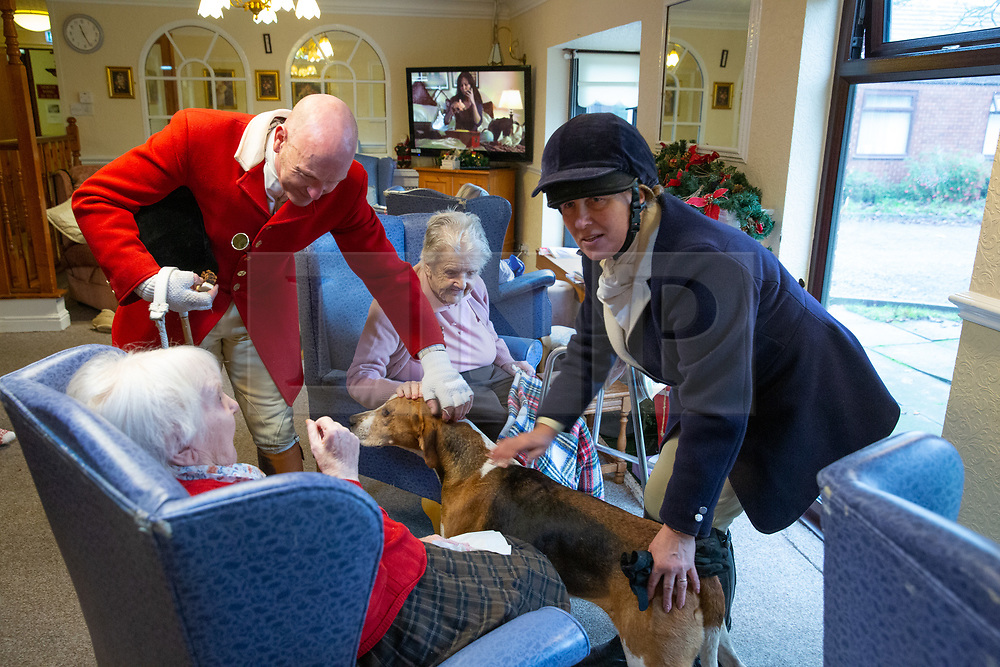 © Licensed to London News Pictures. 26/12/2018. Market Bosworth, UK. Boxing Day Hunt meet. Pictured, the master of the hunt, with hounds, calls into the Orchard Residential home before the parade through the town. The traditional Boxing Day Hunt meet took part in Market Bosworth, Leicestershire, earlier today. Riders of all ages took part in the parade. Meeting in the market square, they visited a near by care home taking their hounds to meet residents. The Hunt formed up in pairs and rode through the town centre passing huge Boxing Day crowds that had come to see the spectacle. Photo credit: Dave Warren/LNP