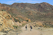 Two people walking in Cabo de Gata national park, Monsul, near San José, Almeria, Spain