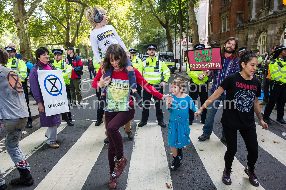 London, UK. 8 October, 2019. Climate activists from Extinction Rebellion dance as they block Millbank on the second day of International Rebellion protests to demand a government declaration of a climate and ecological emergency, a commitment to halting biodiversity loss and net zero carbon emissions by 2025 and for the government to create and be led by the decisions of a Citizens' Assembly on climate and ecological justice.