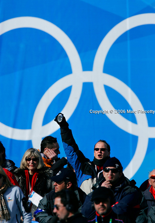 A fan with a small cowbell cheers on the downhill racers in front of a set of Olympic rings at the Men's Downhill of the 2006 Winter Olympics in Sestriere Borgata Sunday February 12, 2006. Fans from every nation were out in force to cheer on their favorite downhiller. The event was won by Antoine Deneriaz of France with a time of 1:48.80, a time that was .72 seconds ahead of silver medalist Michael Walchofer of Austria. American favorites Bode Miller finished fifth with a time of 1:49.93 and teammate Daron Rahlves finished 10th with a time of 1:50.33..(Photo by Marc Piscotty / ©2006)