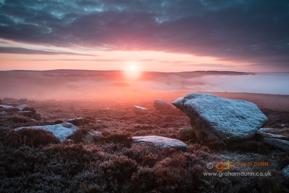 Heavily frosted rocks below Over Owler Tor form the foreground of this atmospheric sunrise scene in the Peak District National Park. The sun, rising over the Longshaw Estate, illuminates lingering mist, giving an orange/red glow to the midground. A colourful winter's morning in Derbyshire, England, UK.