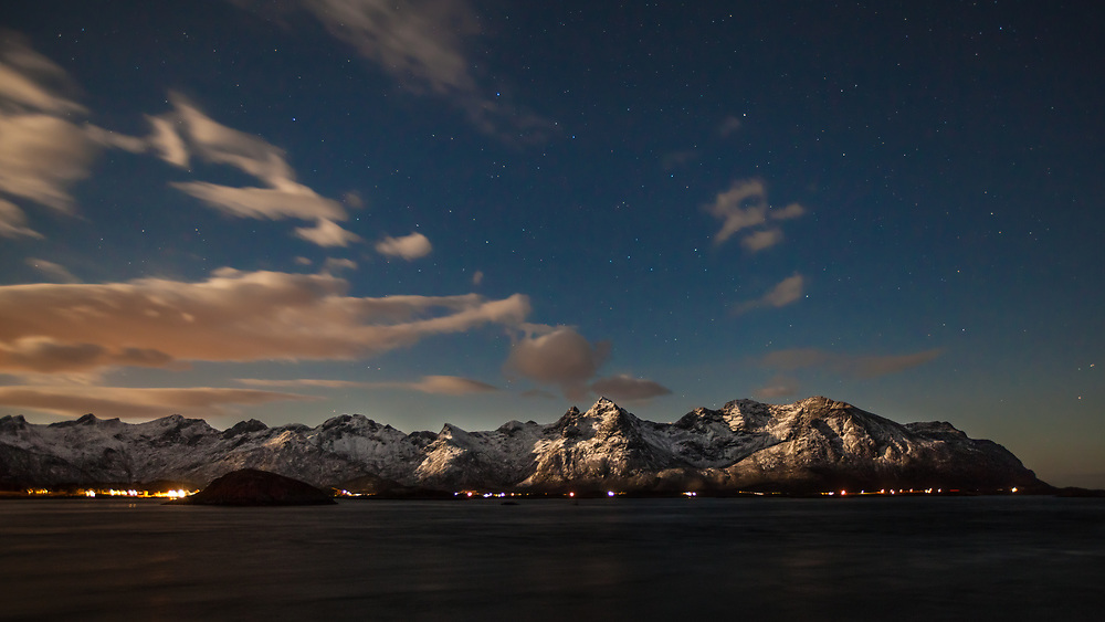 Lofoten Mountain Ridge lit by a full moon at polar night. Lofoten is a district in Norway known for a distinctive scenery with mountains and peaks, open sea and sheltered bays, beaches and untouched lands.
