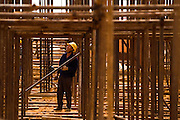 A Chinese worker stands under scaffolding at the construction site of a new 50,000-seat sports stadium in Conakry, Guinea on Friday March 6, 2009.  The project, an investment of about USD 50 million, is a gift to Guinea from the Chinese government.(Olivier Asselin for the New York Times).