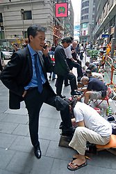 Office workers having shoes shined at lunchtime in Central district of Hong Kong