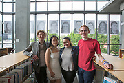 """Photogrpahers  Dean Imel (L) Jessica Wu (2nd L) Mikayla Meadows (2nd R) and Aaron Baker (R) are seen beneath portraits of Skyview students in the windows of the Vancouver Library Thursday  May 17, 2018. Skyview photography students created the public art project called  """"Inside Out""""  The portraits will dominate the streetscape outside the library for a month. (Photo by Natalie Behring for the Columbian)"""