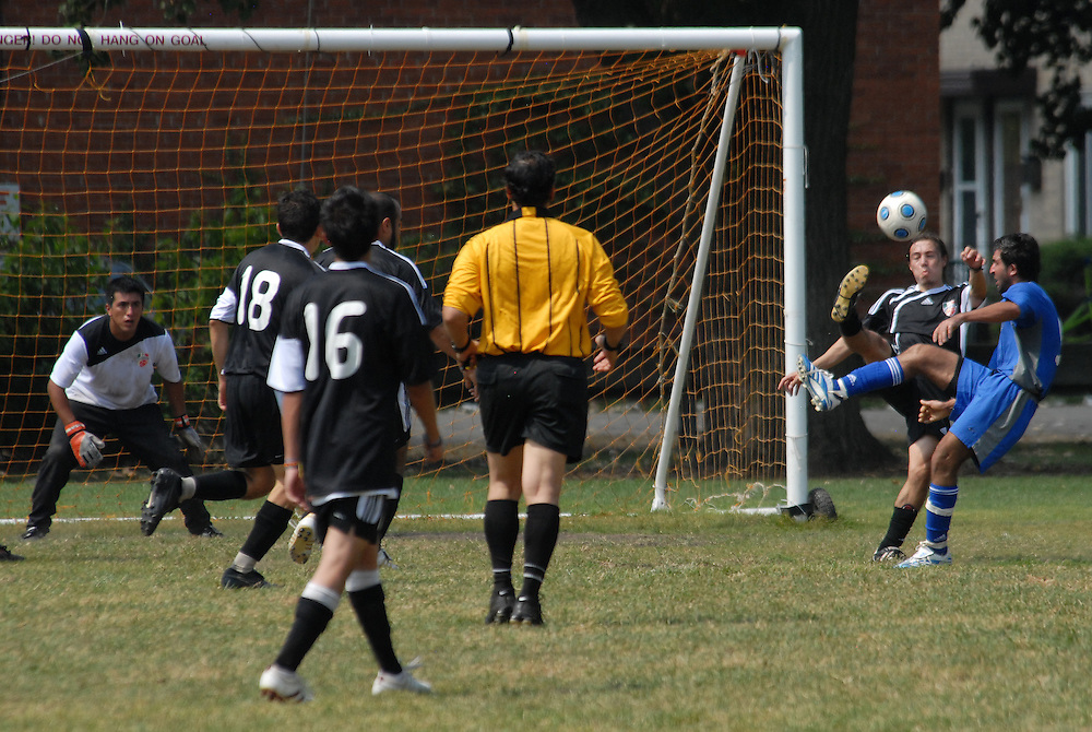 Deportivo Colomex Goalkeeper Jose Cormona (L) looks on as teammate Fabian Ramirez (R) protects his goal against Team Shlama (Blue) during National Soccer League play in Skokie, Il.