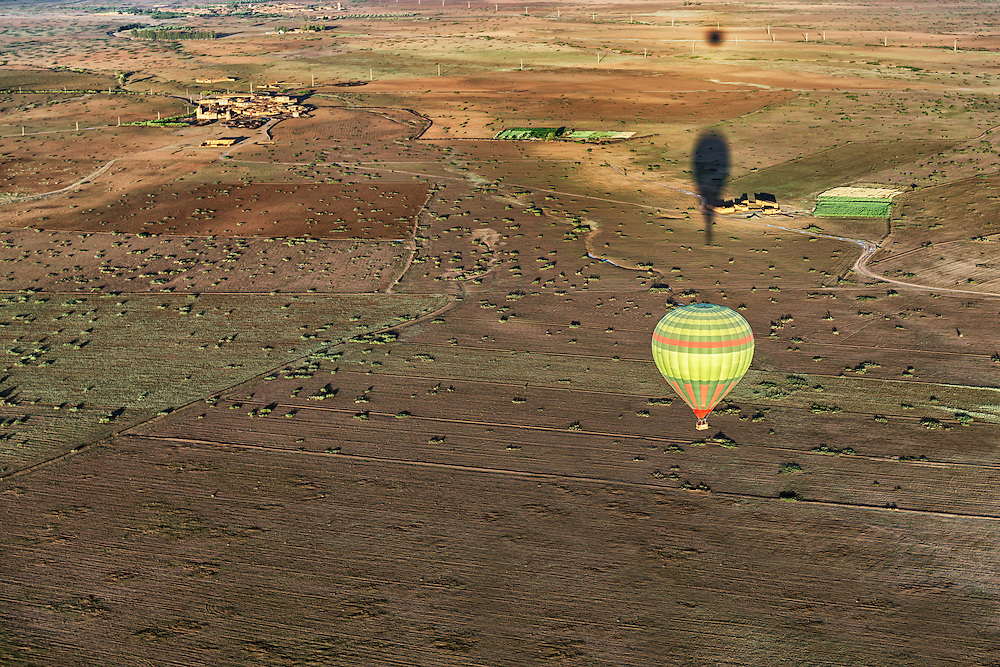 Hot-air balloon with shadows over rural Marrakech, Morocco.