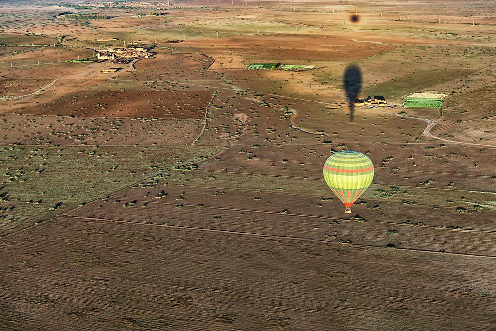 Hot-air balloon with shadows over rural Marrakech, Morocco.