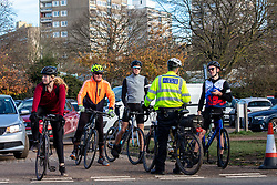 © Licensed to London News Pictures. 22/11/2020. London, UK. A police officer chats with cyclists and walkers as they exercise during Lockdown 2.0 in Richmond Park, South West London. The Prime Minister is expected to address the Nation tomorrow to set out his plans for Christmas and the end of lockdown 2.0 on the 2nd of December 2020 with the opening up of shops, pubs and restaurants. However it is believed he will also introduce a new tougher three-tiered system with further localised restriction. Photo credit: Alex Lentati/LNP