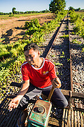 29 JUNE 2013 - BATTAMBANG, CAMBODIA:  A bamboo train on the tracks near O Sra Lav, a small village southeast of Battambang. The bamboo train, called a norry (nori) in Khmer is a 3m-long wood frame, covered lengthwise with slats made of ultra-light bamboo, that rests on two barbell-like bogies, the aft one connected by fan belts to a 6HP gasoline engine. The train runs on tracks originally laid by the French when Cambodia was a French colony. Years of war and neglect have made the tracks unsafe for regular trains.  Cambodians put 10 or 15 people on each one or up to three tonnes of rice and supplies. They cruise at about 15km/h. The Bamboo Train is very popular with tourists and now most of the trains around Battambang will only take tourists, who will pay a lot more than Cambodians can, to ride the train.       PHOTO BY JACK KURTZ