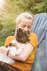 Young woman embracing dog in the domestic garden and smiling, Munich, Bavaria, Germany