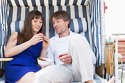 Couple eating strawberries in roofed wicker beach chair