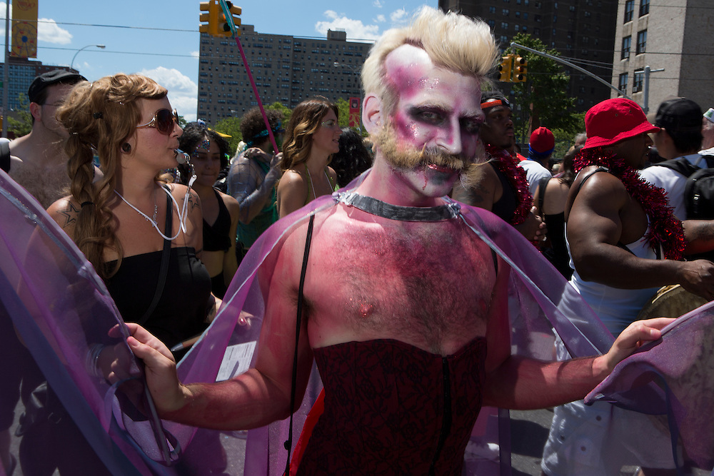 A man in a burgundy corset, a violet shawl, and matching makeup. While the theme of the parade is mermaids, the theme was interpreted loosely, and often ignored.