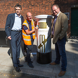 Local councillors Paul Swaddle, left and Robert Rigby with Tony Newlin for Royal Mail as he applies the vinyl decals ahead of Royal Mail unveiling a white-painted postbox outside Lords Cricket Ground with a plaque and graphics that celebrate England's ICC Cricket World Cup Victory. London, July 16 2019.