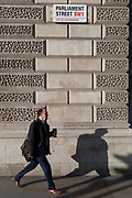 A man walking in the direction of Whitehall, carries a drinks cup beneath the signpost for Parliament Street SW1, Westminster, on 29th January 2020, in London, England.
