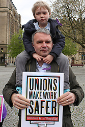 April 28, 2018 - Manchester, Lancashire, United Kingdom - A father carries his young son on his shoulders whilst his sign reads ''Unions make Work Safer'' at the International Workers Memoriial Day rally in Manchester city centre. This day (April 28th) each year commemorates all workers rights worldwide. (Credit Image: © Andrew Mccoy/SOPA Images via ZUMA Wire)
