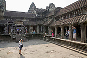 Tourists explore and photograph within one of the galleries in the ancient temple complex of Angkor Wat, Siem Reap, Cambodia.  Angkor Wat is one of UNESCO's world heritage sites. It was built in the 12th century and covers 162 hectares.  It is Cambodia's main tourist attraction.