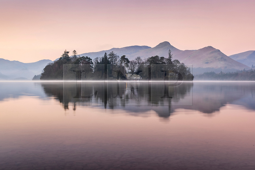 © Licensed to London News Pictures. 02/03/2021. Keswick UK. Derwent Isle reflects into the calm water off Derwent Water at dawn this morning in Cumbria. Photo credit: Andrew McCaren/LNP