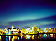 A bright, active aurora borealis fills the sky over the South Saskatchewan River and downtown Saskatoon