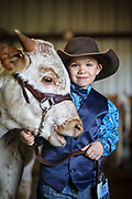 SHOT 1/24/20 3:46:41 PM - Mick Velazquez, 5, of Douglas, Wyo. poses for a portrait with Belle Jewel, the 8 month old female Longhorn he was showing, at the National Western Stock Show. The National Western has been held annually every January at the National Western Complex in Denver, Colorado since 1906. Its purpose is to demonstrate better breeding and feeding techniques to attendees. Since first held in 1906, it has become the world's largest stock show by number of animals and offers the world's only carload and pen cattle show. (Photo by Marc Piscotty / © 2020)
