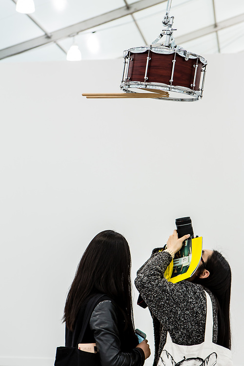 New York, NY - 5 May 2017. The opening day of the Frieze Art Fair, showcasing modern and contemporary art presented by galleries from around the world, on Randall's Island in New York City. A woman takes a photo of an installation of drums, this one suspended upside down, which appear to play themselves, by Anri Sala, in the Marian Goodman Gallery.