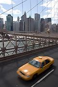 A tipical New York's yellow cab runs through Brooklyn bridge at high speed. <br /> <br /> Un taxi amarillo, típico de Nueva York cruza a toda velocidad el puente de Brooklyn, con Manhattan al fondo.