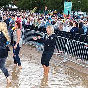 NLD/Almere/20180825 - Festival Zand 2018, publiek staat in het water na een regenbuir