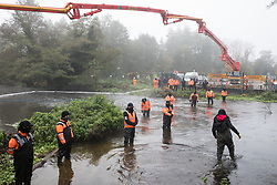 HS2 security guards monitor an anti-HS2 activist wading in the river Colne at Denham Ford in order to try to delay bridge building works for the HS2 high-speed rail link on 5 November 2020 in Denham, United Kingdom. Prime Minister Boris Johnson has advised that construction work may continue during the second national coronavirus lockdown but those working on construction projects are required to adhere to Site Operating Procedures including social distancing guidelines to help prevent the spread of COVID-19.
