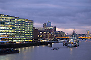 Night scene looking over the River Thames towards HMS Belfast and More London area offices and business district in London, United Kingdom. This area is a recent development which is now thriving and bustling with more buildings being constructed in this moderm glass style and filling the area with office workers.