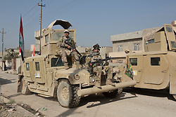 Licensed to London News Pictures. 11/11/2016. Mosul, Iraq. Soldiers, of the Iraqi Army's 9th Armoured Division, sit on an armoured Humvee as it drives along a road during a visit to Mosul's Al Inisar district on the south east of the city. The Al Intisar district was taken four days ago by Iraqi Security Forces (ISF) and, despite its proximity to ongoing fighting between ISF and ISIS militants, many residents still live in the settlement without regular power and water and with dwindling food supplies.<br /> <br /> The battle to retake Mosul, which fell June 2014, started on the 16th of October 2016 with Iraqi Security Forces eventually reaching the city on the 1st of November. Since then elements of the Iraq Army and Police have succeeded in pushing into the city and retaking several neighbourhoods allowing civilians living there to be evacuated - though many more remain trapped within Mosul.  Photo credit: Matt Cetti-Roberts/LNP