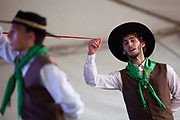 Young men boys teenagers, dancing on stage in couples, wearing traditional Gaucho dancing costumes for a performance. Reponte da Cancao music festival and song competition in Sao Lorenzo do Sul, RIo Grande do Sul, Brazil.