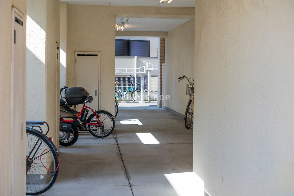 open hallway with parked bycicles under a residential  building Japan Yokosuka