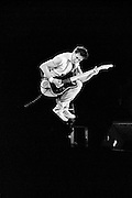 Pete Townshend of The Who playing guitar full airborne