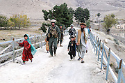 """US Marine Colonel Jeff Haynes, Commanding Officer, 201st Regional Corps Advisory Command, with advisors and Afghan villagers crossing a bridge entering the Tagab Valley.   ....One of the main tactics is a new road through Tagab Valley that will allow traffic to bypass Kabul providing a more direct link between Pakistan and destinations north including Uzbekistan and Tajikistan.....To win the Tagab Valley, Colonel Haynes said, """"The creeping barrage of goodness, really centers on the road going up the valley, because then you can begin development projects and increase prosperity.  The cab fare for villagers went from $8 down to $1 just because the ANA graded the road.""""  As the ANA move north through the valley they are building combat outposts to sustain the gains.  Haynes confirmed this is an ANA campaign - the first of its kind - his soldiers are mentoring the ANA, there are no coalition troops.  .."""
