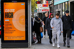 © Licensed to London News Pictures. 26/10/2020. London, UK. Men walk past a COVID-19 high alert level sign in north London. It has been reported that the government is planning for an extra tougher fourth tier of Covid-19 restrictions in England if coronavirus cases increase in the coming weeks. The measures could see restaurants, pubs and non-essential businesses such as clothes shops forced to close in areas where tier 3 rules have not brought the virus under control. Currently all 32 boroughs plus the City of London are in tier two, where there is a high risk of coronavirus. Photo credit: Dinendra Haria/LNP